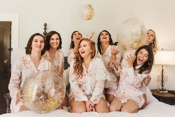 bride and bridal party having some fun in the room at Crane Cottage