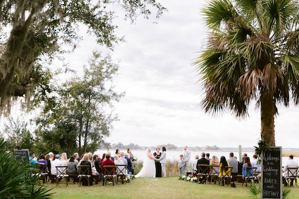 Two brides exchanging wedding vows at their Saint Simons Island wedding on the banks of the Frederica River