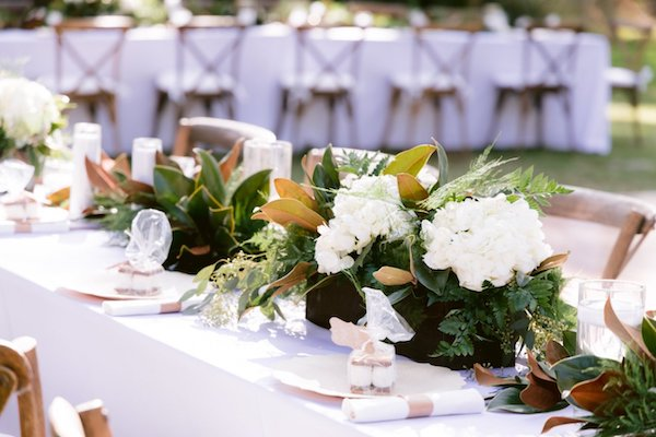 Long reception tables with white linen and centerpieces of greenery, magnolia leaves and white flowers