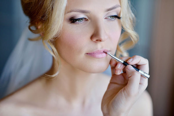 makeup artist applying lipstick to a bride