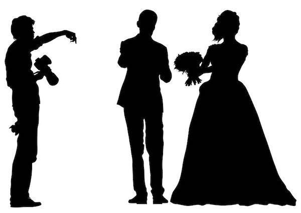 silhouette of a photographer giving direction to a bride and groom