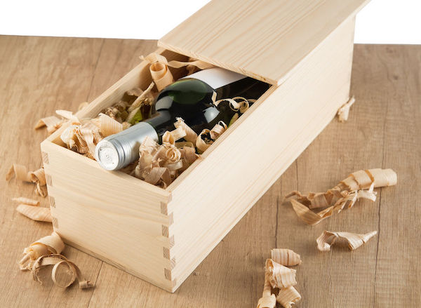 a wooden box with a bottle of red wine for service at a wedding