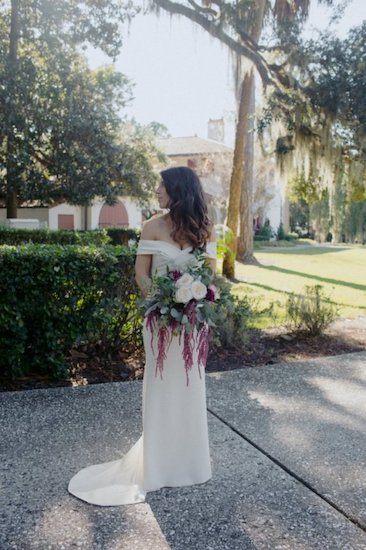 bride wearing a form fitting, off the shoulder wedding gown with a criss cross bodice detail