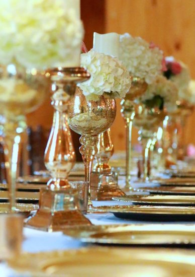 wedding reception table filled with gold toned candelabras, goblets and white flowers with lush linens and gold charger plates perfect for a Bridgerton themed wedding