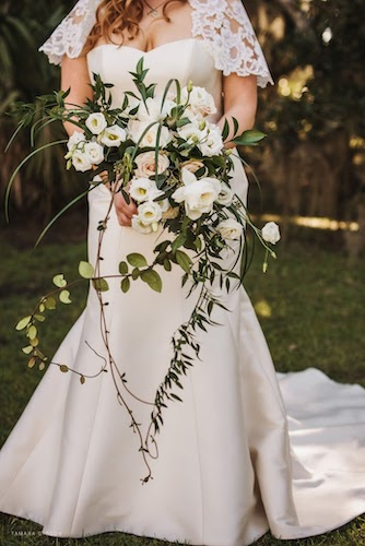 bride carrying a loose European styled bridal bouquet with white roses