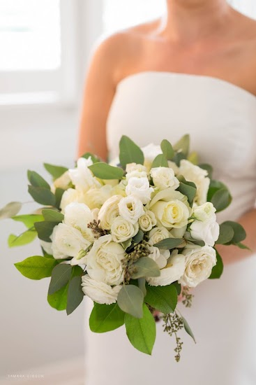 bride holding a Boho-inspired bridal bouquet with white roses, lisianthks and ranunculus