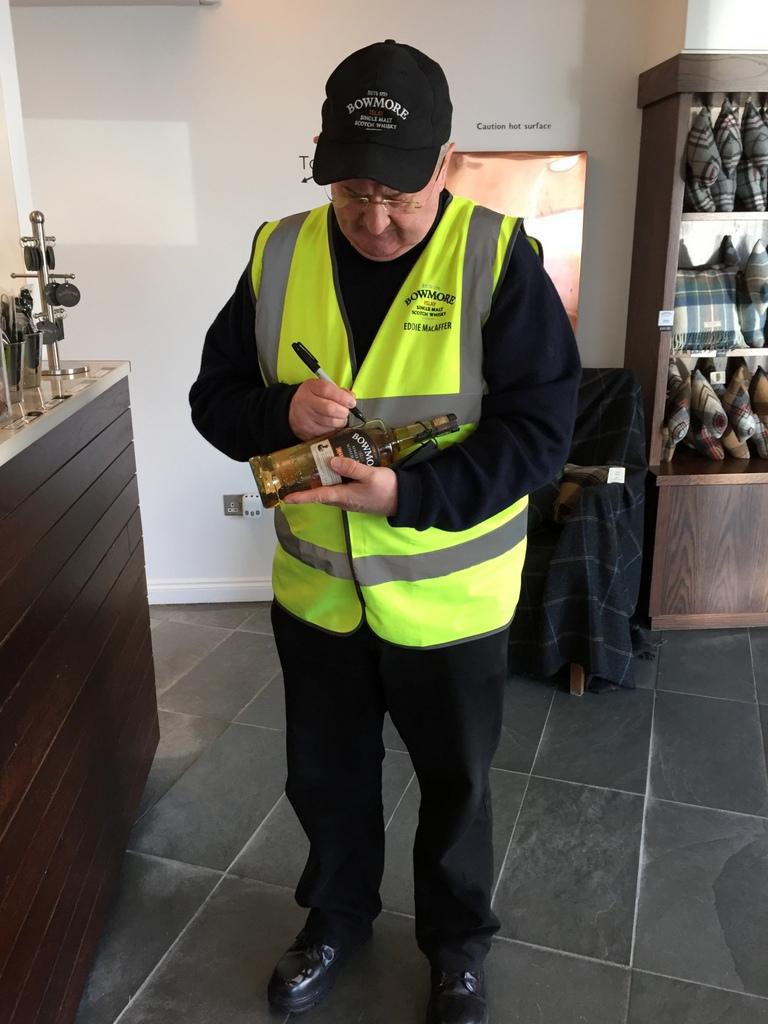 Eddie MacAffer signs my bottle at Bowmore distillery