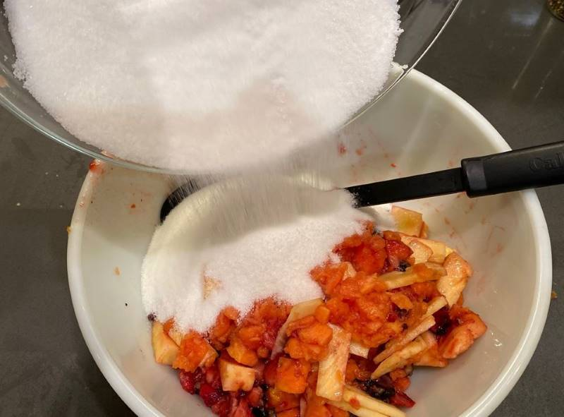 Adding fruit and sugar to make fassionola