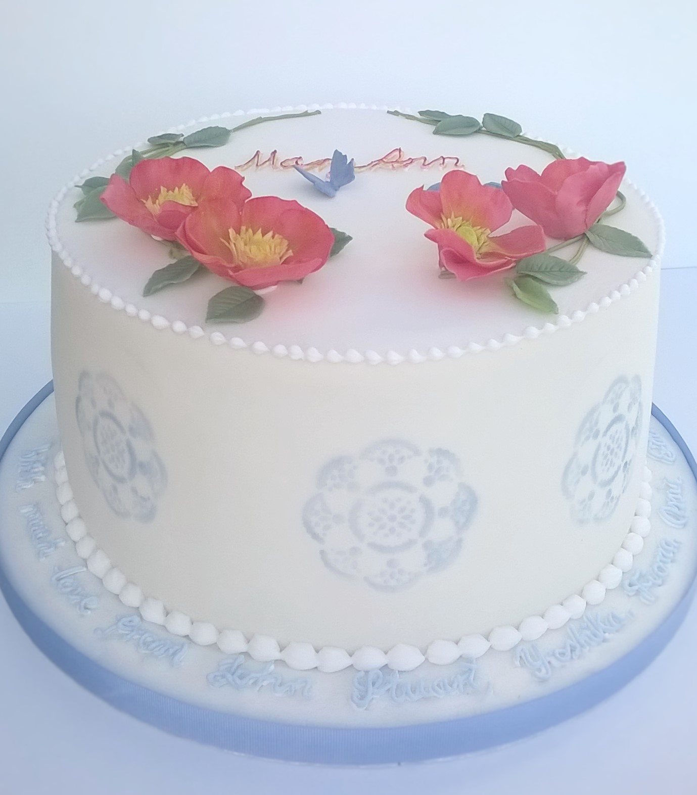 White party cake with blue stencilling and sugar roses