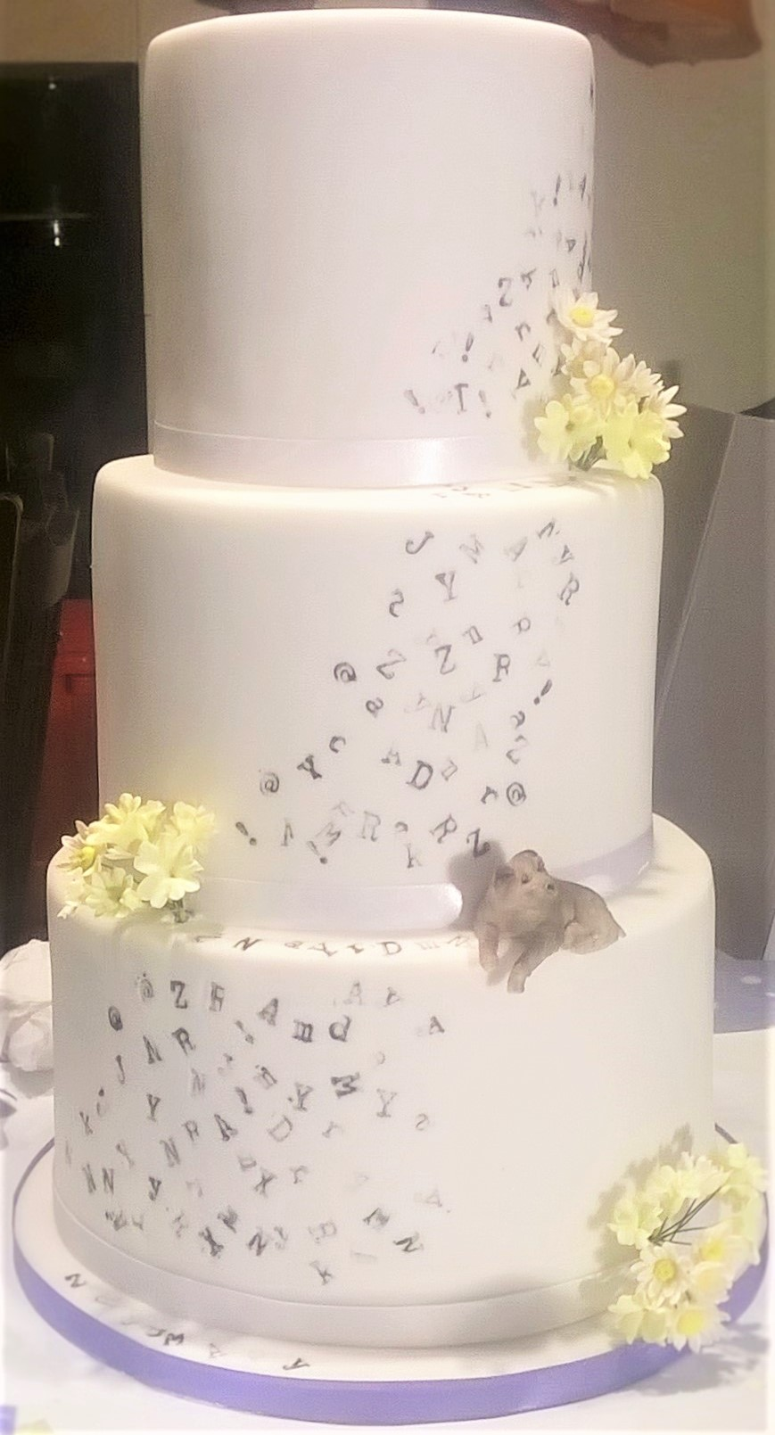 Tiered party cake with sugar flowers and sugar dog