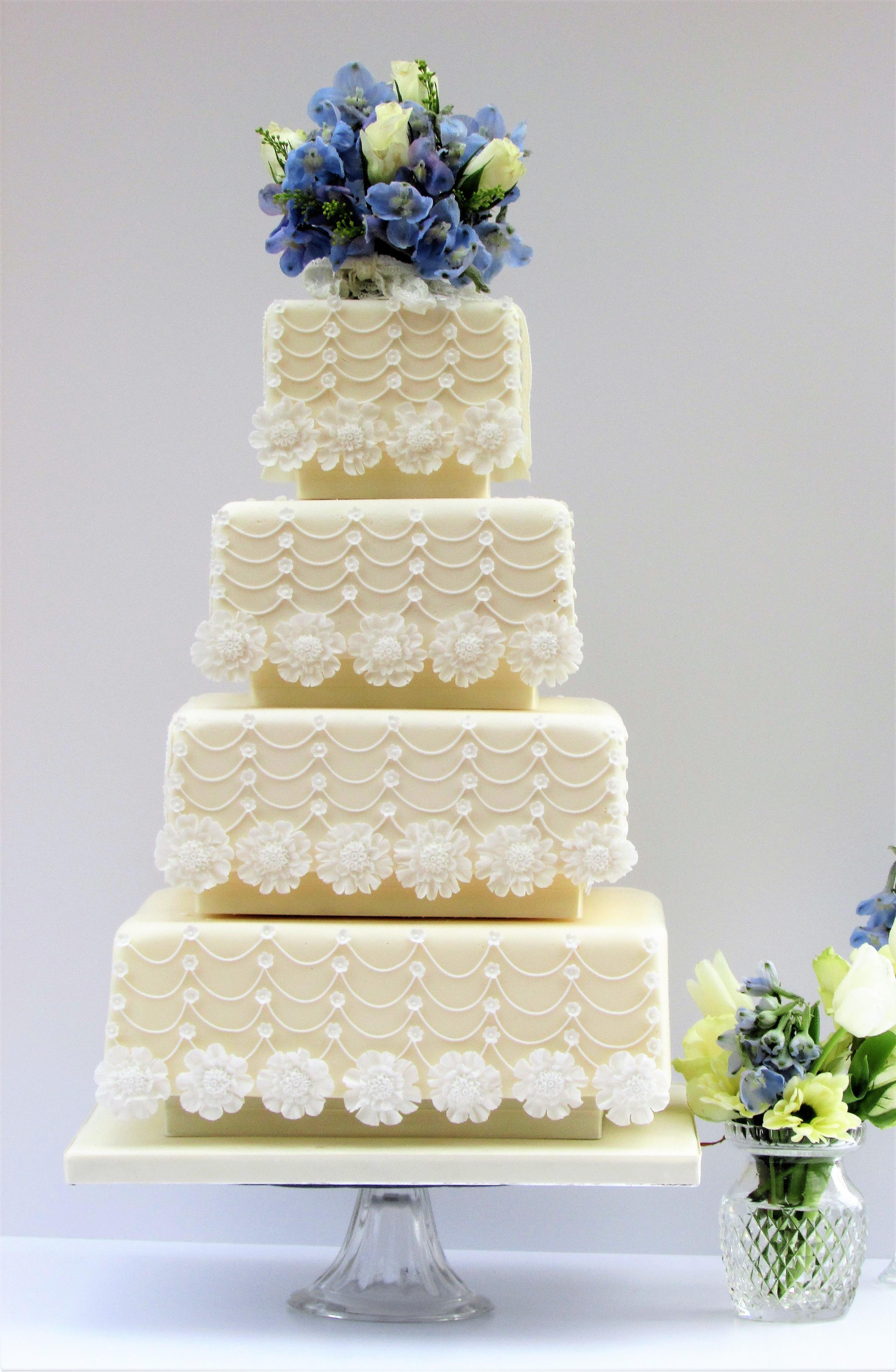 Tiered cream wedding cake with sugar flowers