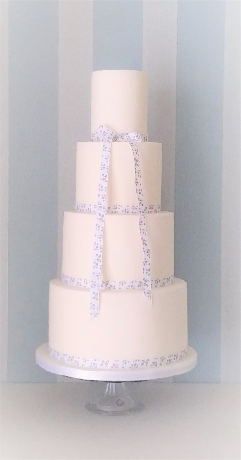 4 tier white wedding cake with blue and white floral ribbons by Cocoa & Whey Cakes in Dorset