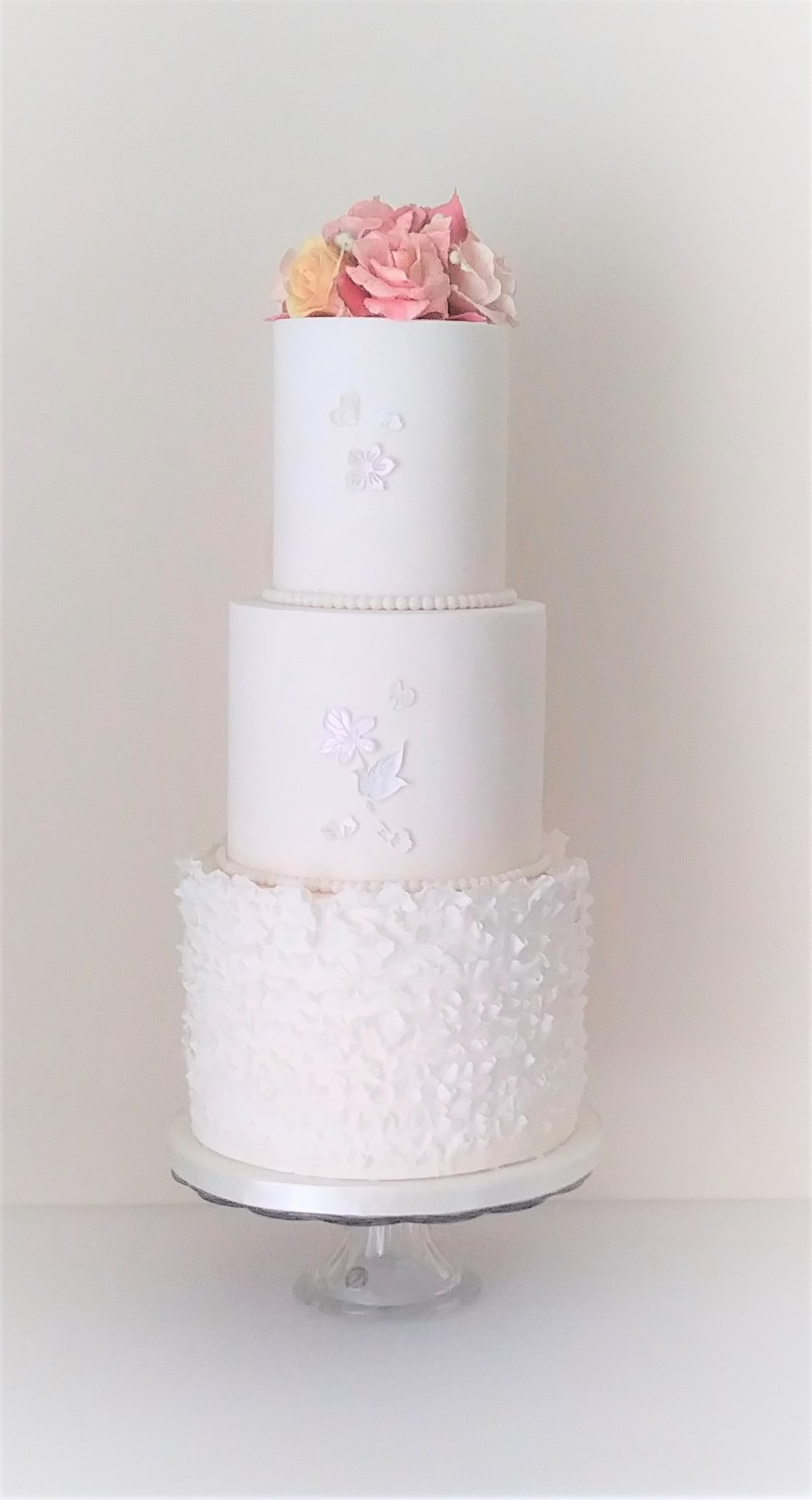3 tier cream wedding cake with ruffles and sugar roses by Cocoa & Whey Cakes in Dorset
