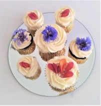 Cupcakes topped with swirls of buttercream and fresh petals and cornflowers