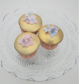 Gold lustre cupcakes with sugar hydrangea blossoms in pink and blue