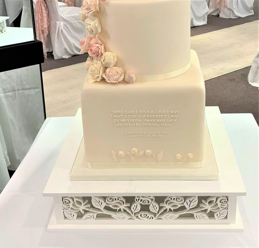 Close up of Ivory Wedding Cake with Sugar Roses and Chaucerian Quote
