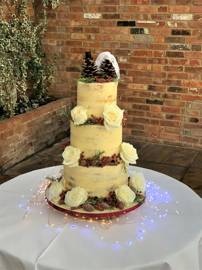 Festive Semi-Naked Wedding Cake with Chocolate Pine Cones by Cocoa & Whey Cakes in Dorset