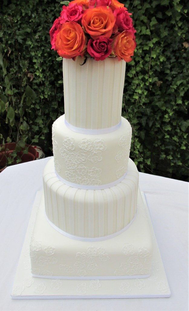 Tall White Striped Wedding Cake and Fresh Roses
