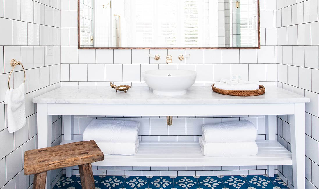 White-bathroom-subway-tile-blue-cement-tile-floor-brass-plumbing-faucet-cococozy-halcyonhouse