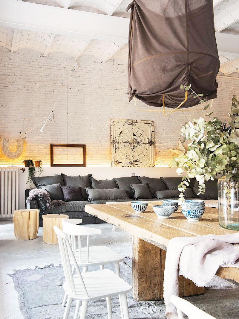 bright barcelona apartment tour living room grey linen sofa farm table dining room white farm chairs