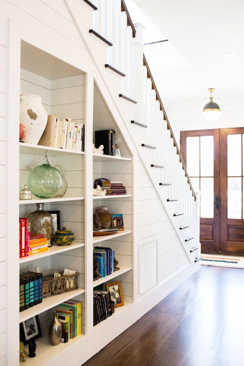 entry way built in bookshelves under staircase bright books wooden floors