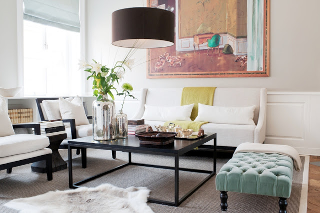 Large black pendant light over a coffee table with white sofas living room interior design