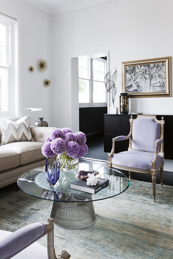 Contemporary living room with lavender Louis XIV chairs, a Saarinen inspired coffee table with a glass top and purple hydrangenas