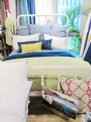 Bed with white iron frame and blue, white and green pillows and sheets