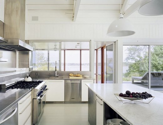 Kitchen in a Montauk on Long Island lake house with large windows, a sliding glass door, stainless appliances, white drawers with long silver drawer pulls and white pendant lights