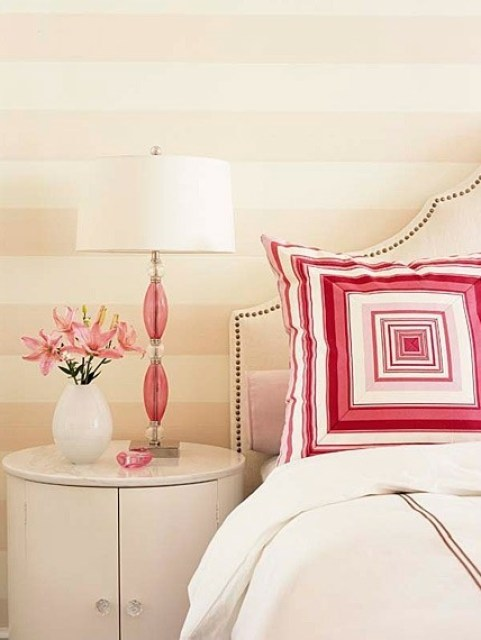 Bedroom with white upholstered headboard, a round night stand, pink and white lamp with a glass base, a graphic pillow and striped wall