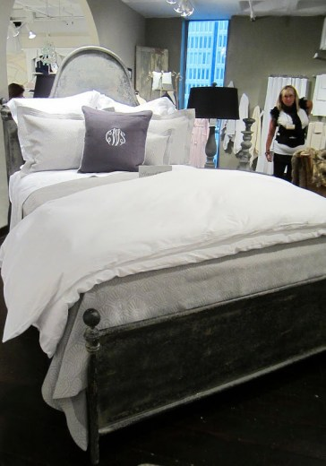 bed from Peacock Alley with grey and white bedding on an iron bed frame