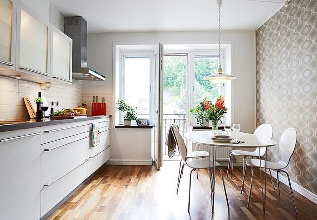 small kitchen with long cabinet drawers with long pulls, ceramic backsplash, one wall covered in wall paper, pendant light and wood floor.