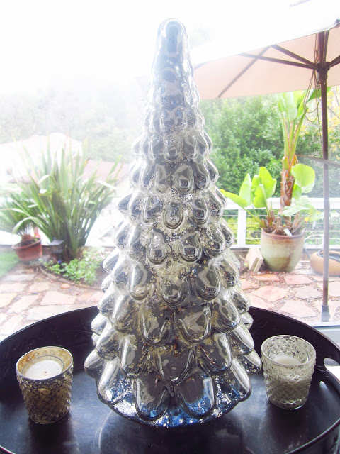 Mercury glass Christmas tree in a kitchen window overlooking a backyard with a candle on each side