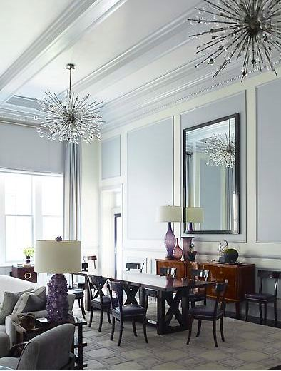 Dining room by Steven Gambrel with high coffered ceilings and decorative molding, two modern chandelier, grey-lavender painted walls to created a panel effect, floor length curtains,  a greyish lavender area rug covered in squares.