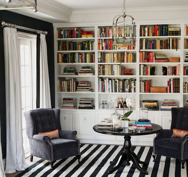 library with white built in bookshelves, black and white striped rug, velvet wing back armchairs, round wooden table, black wall with white floor length curtains