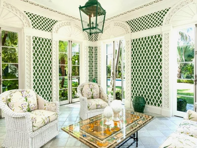 Sun room in a Palm Beach estate with wicker furniture and white and green trellis walls