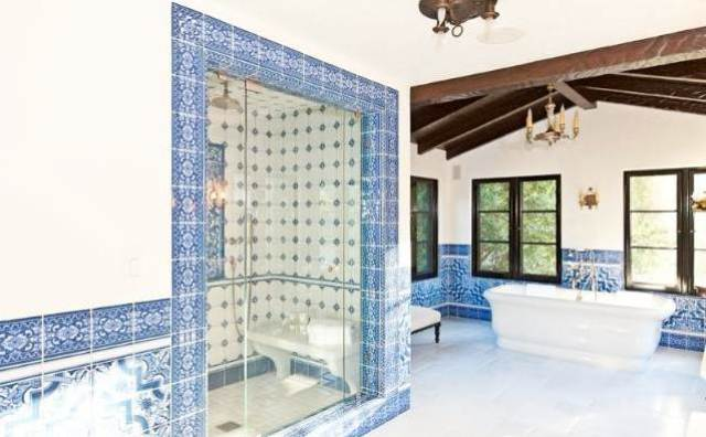 shower with blue and white tiles and bench