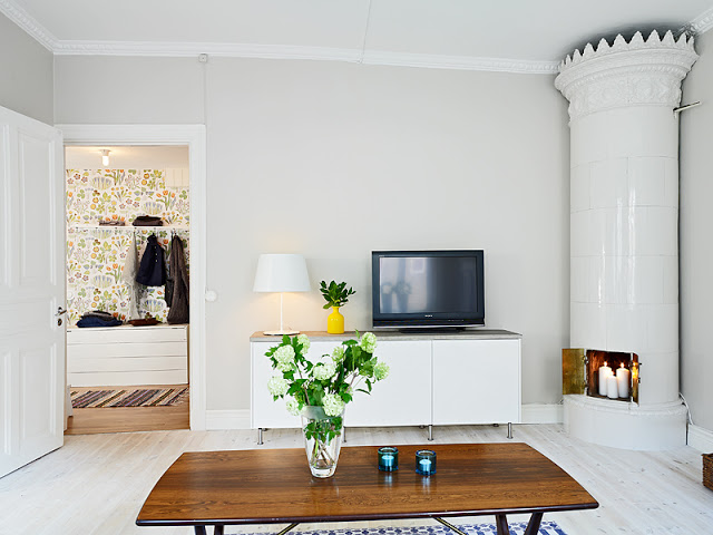Alternative view of the living room with light wood floors, neutral light gray walls, and white furnishings