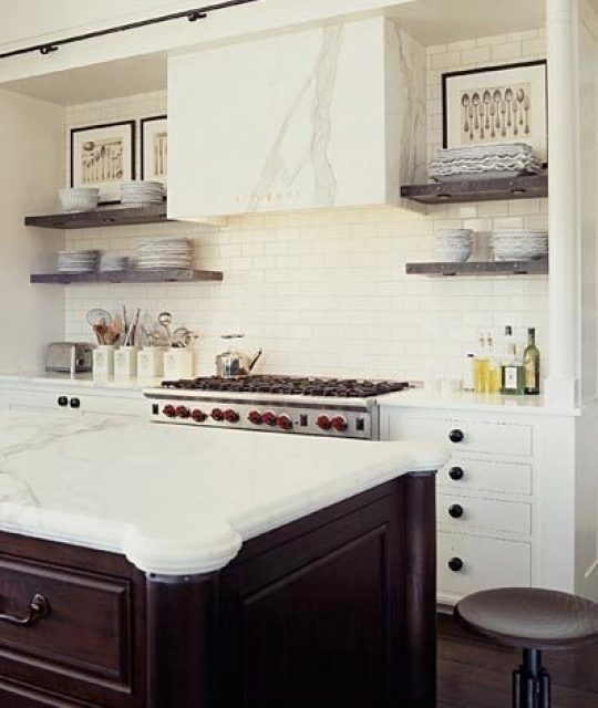 kitchen with a marble slab range hood cover, subway tile backsplash, black drawer pulls, an industrial stool and a wood island