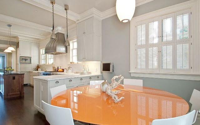 Breakfast nook with round orange table surrounded by white chairs, dark wood floor, grey walls, pendant lights, white countertops with matching cabinets and a wood island
