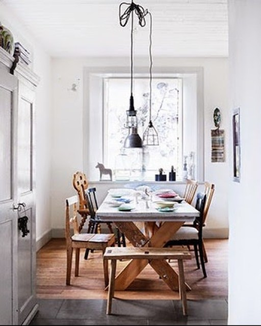 Dining room with mismatched chairs and industrial style lights