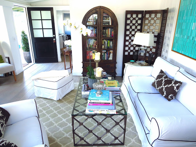 Coco of COCOCOZY's living room with white slip covered sofa, ottoman and armchair with brown trim and a COCOCOZY rug