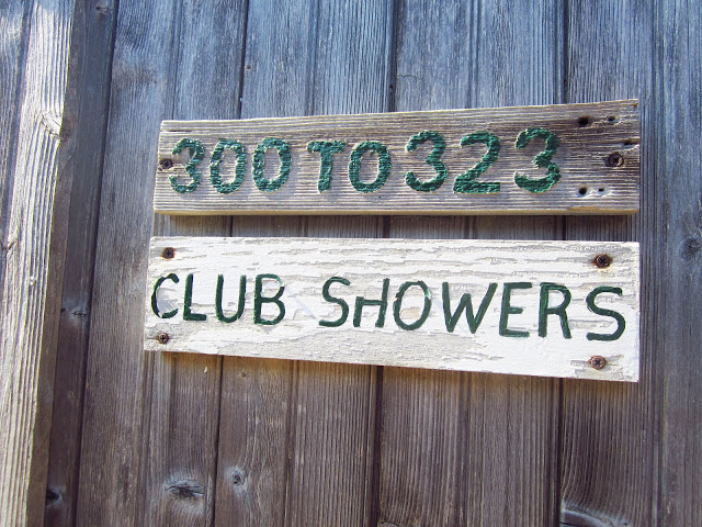 "wood sign that says ""300 to 323"" with a second wood sign below it saying ""CLUB SHOWERS"""