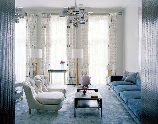 Patel living room in london with a blue velvet sofa, tufted lavender armchairs, blue carpet and a modern chandelier