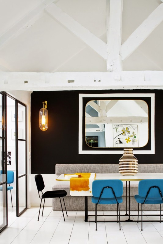Dining room in a Paris apartment with exposed beams and black accent wall