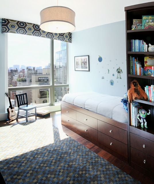 twin bed with drawers and a bookshelf attached, wood floor with rug covered in multicolored squares and a large window with aview of a city