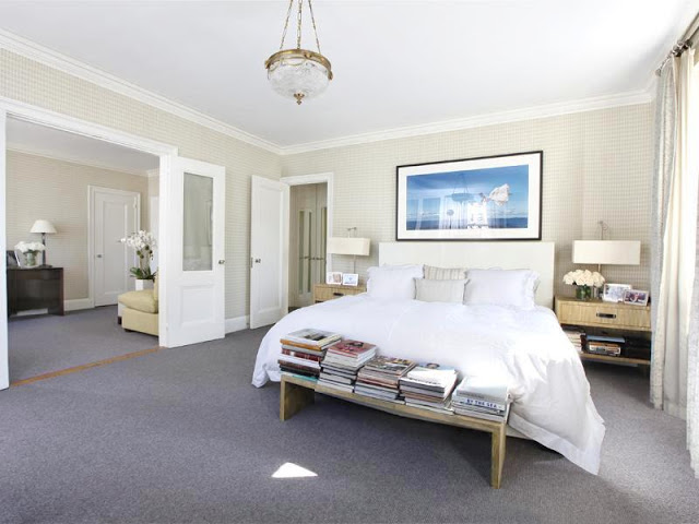 Bedroom with crystal pendant light, grey carpet, two wicker nightstands, and a bench at the foot of the bed holding stacks of books