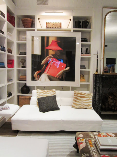 Close up of a piece of art in the Windsor house's family room. It's of a woman in a wood chair holding a red book and wearing a red hat. The piece is in front of a the built in bookshelves and above the what Barcelona club chairs