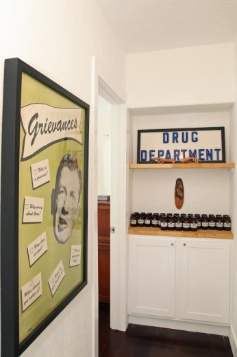 Hall leading to the bedrooms with vintage posters, signs and a shelf of jars