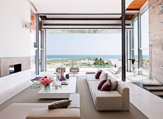 ultra modern living room with retractable wall, fireplace, long sofa and armchair with a view of the ocean